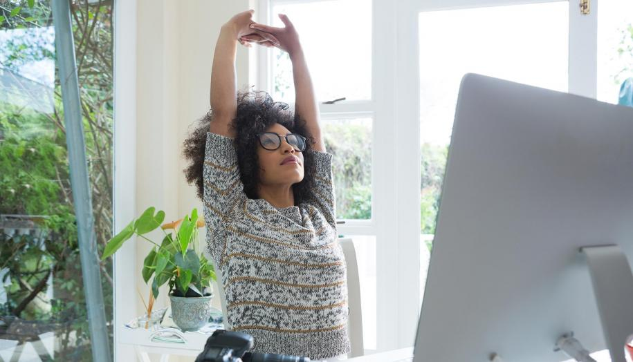 Image: Woman stretching at desk